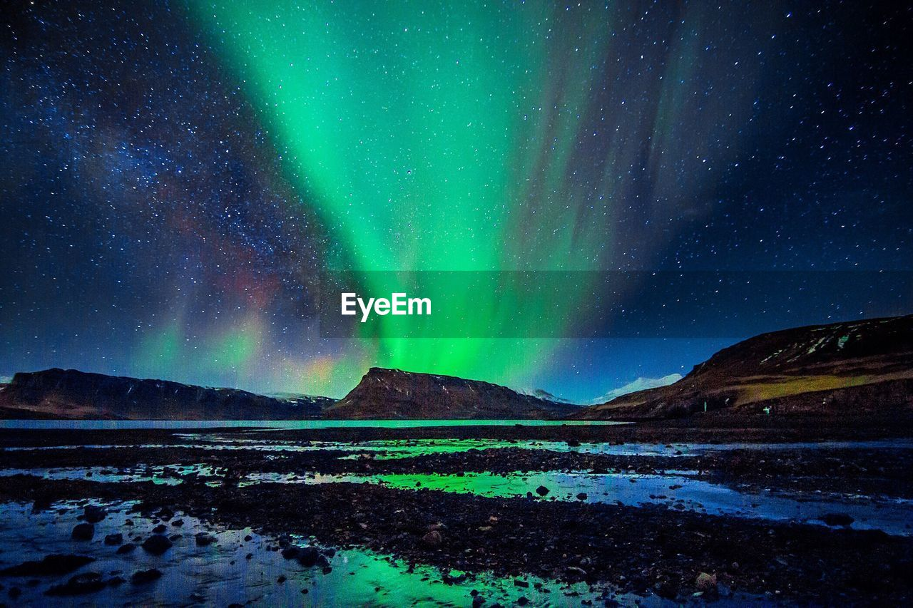 Scenic View Of Star Constellation And Aurora Over Landscape