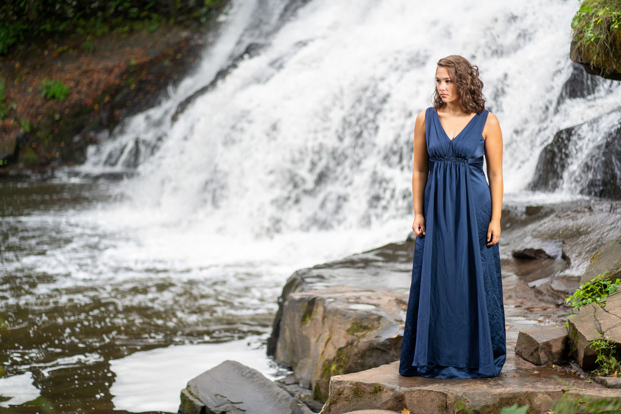 water, young adult, young women, full length, motion, nature, waterfall, real people, flowing water, women, people, portrait, scenics - nature, lifestyles, splashing, front view, day, standing, solid, fashion, outdoors, beautiful woman, hair, hairstyle, flowing