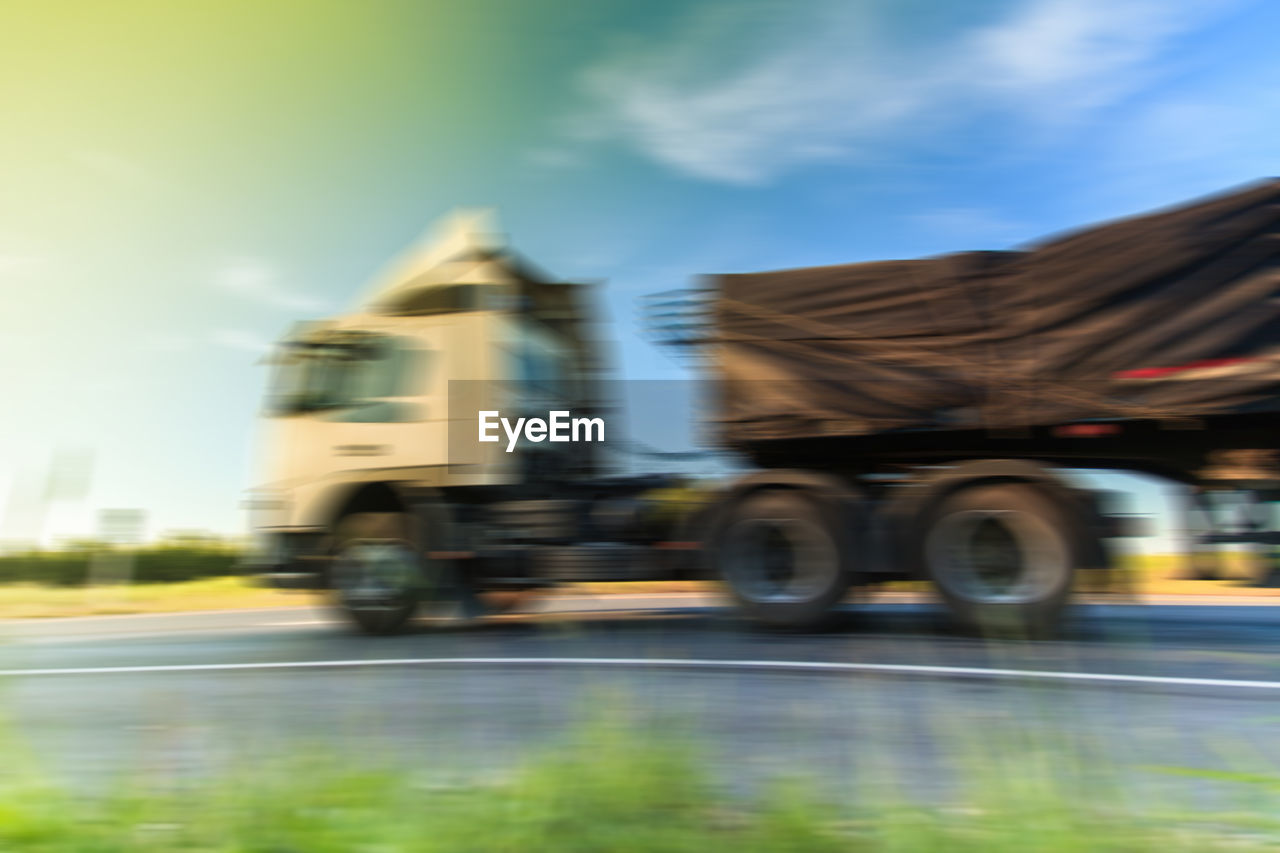 transportation, blurred motion, speed, mode of transport, road, motion, day, sky, outdoors, land vehicle, city, no people