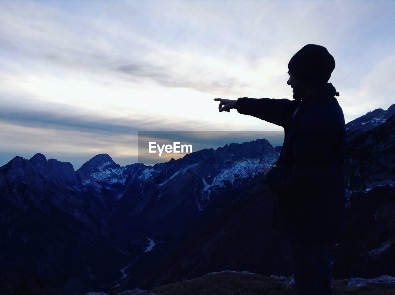 one person, mountain, sky, standing, leisure activity, real people, scenics - nature, activity, men, lifestyles, three quarter length, beauty in nature, side view, nature, non-urban scene, holding, silhouette, cloud - sky, tranquility, mountain range, outdoors