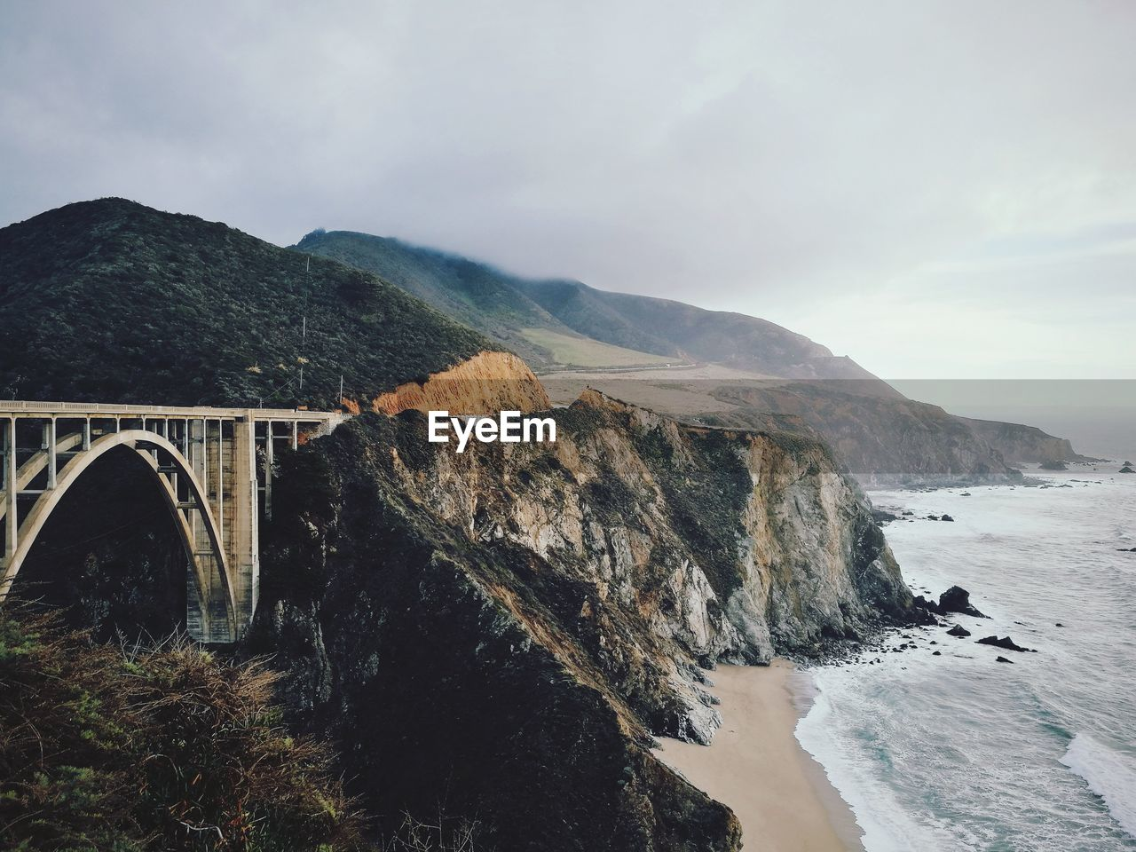 ARCH BRIDGE OVER SEA AGAINST MOUNTAINS