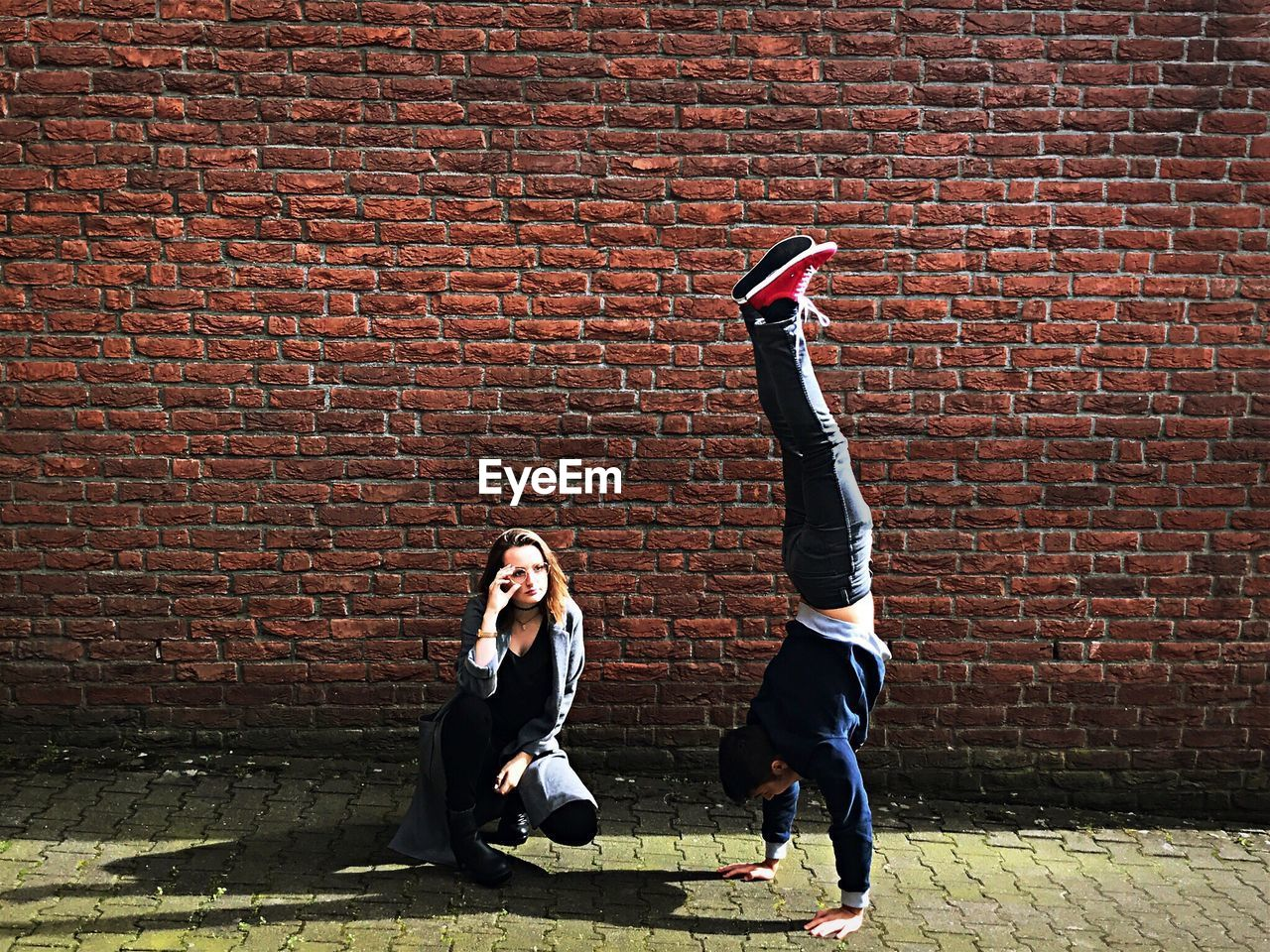 Woman Looking At Man Practicing Handstand Against Brick Wall