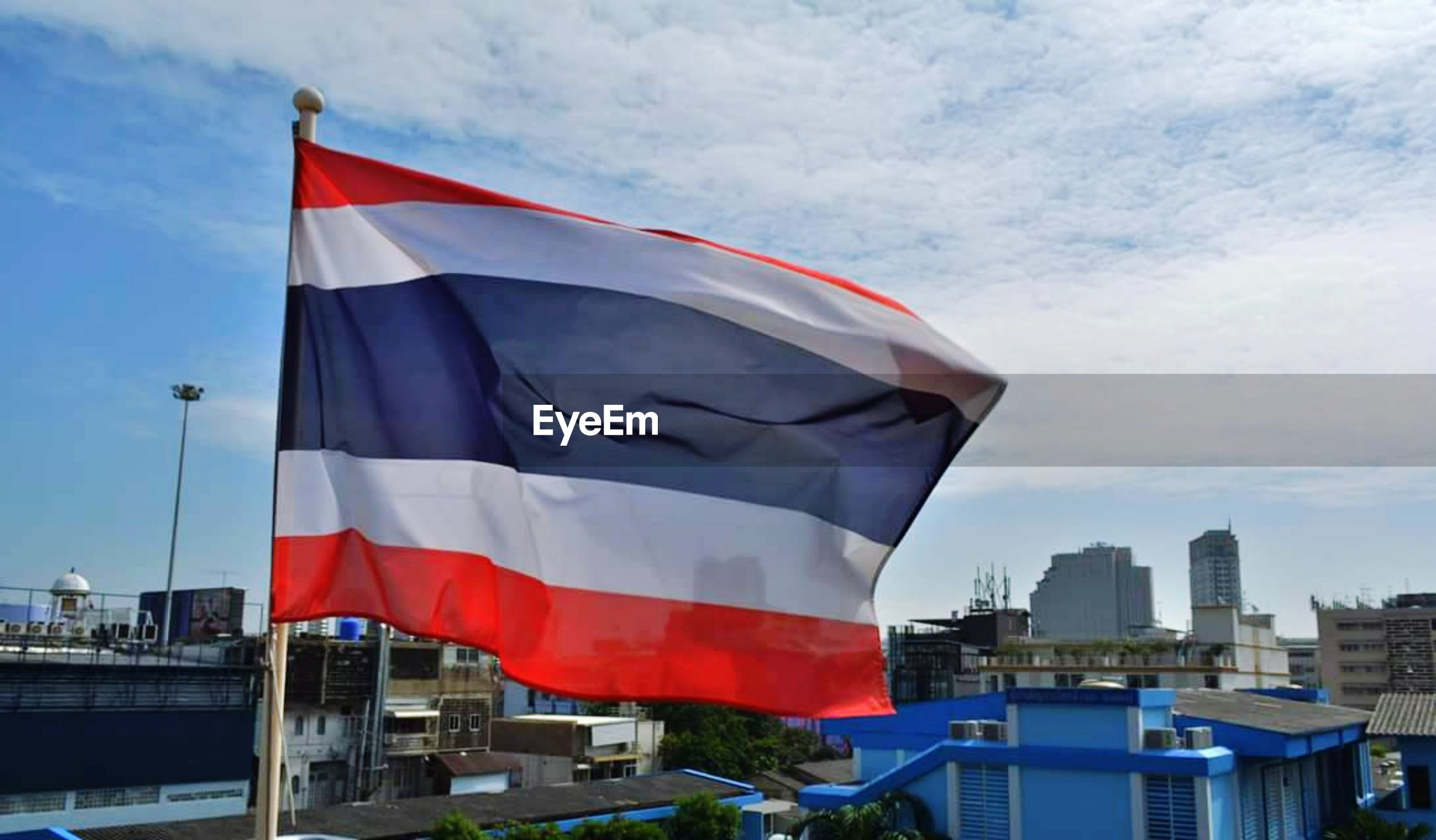 Flag in city against cloudy sky