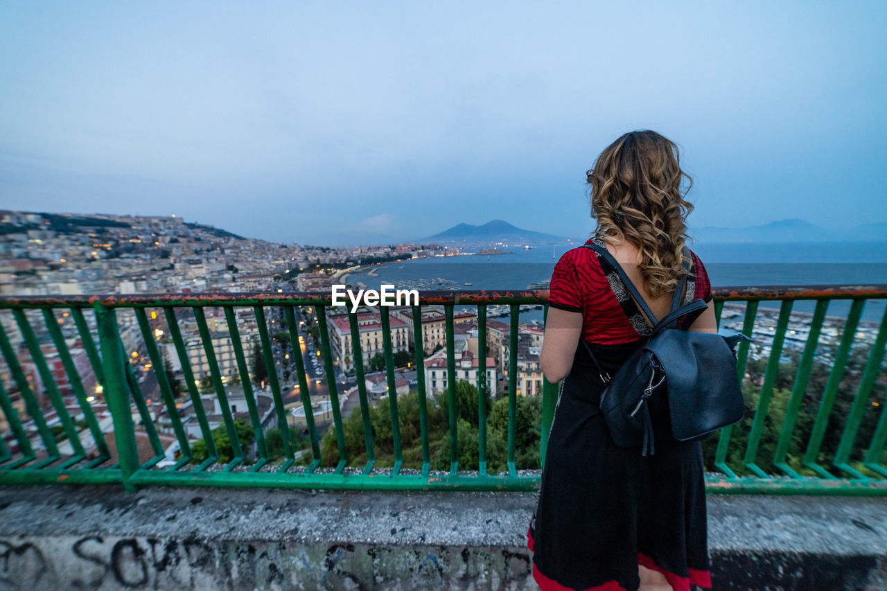 one person, real people, railing, lifestyles, mountain, standing, young women, young adult, sky, leisure activity, nature, scenics - nature, water, women, casual clothing, clothing, day, beauty in nature, hair, hairstyle, looking at view, outdoors