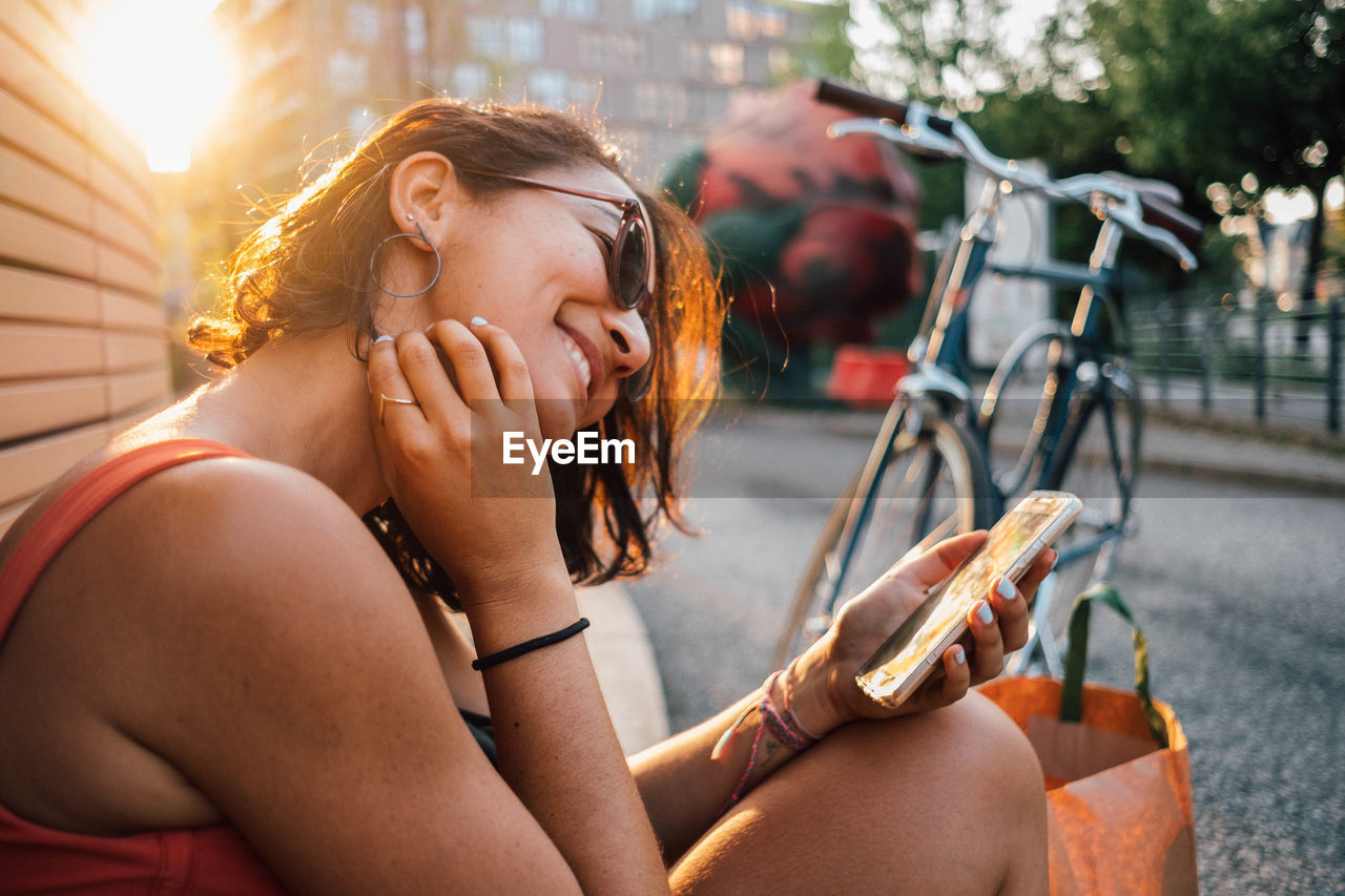 Close-up of smiling woman using mobile phone while sitting outdoors