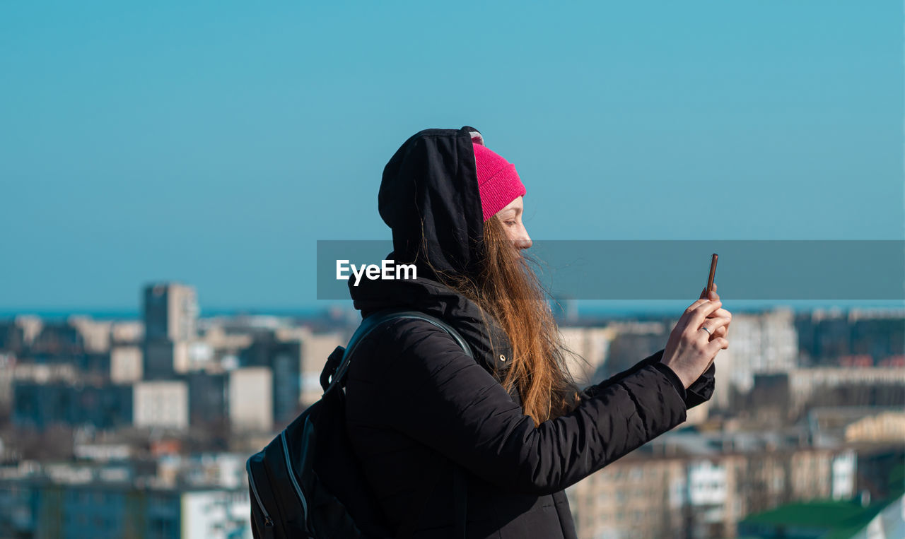 Confident woman in pink hat with smartphone in hand calling friend walking city background blue sky