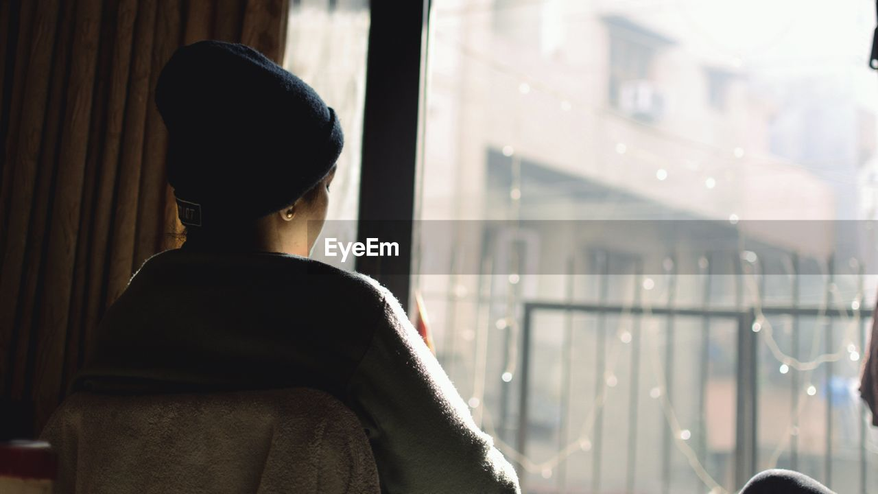 one person, window, real people, rear view, lifestyles, leisure activity, waist up, headshot, focus on foreground, hat, glass - material, architecture, looking, day, standing, built structure, clothing, building exterior, transparent, outdoors, warm clothing, contemplation