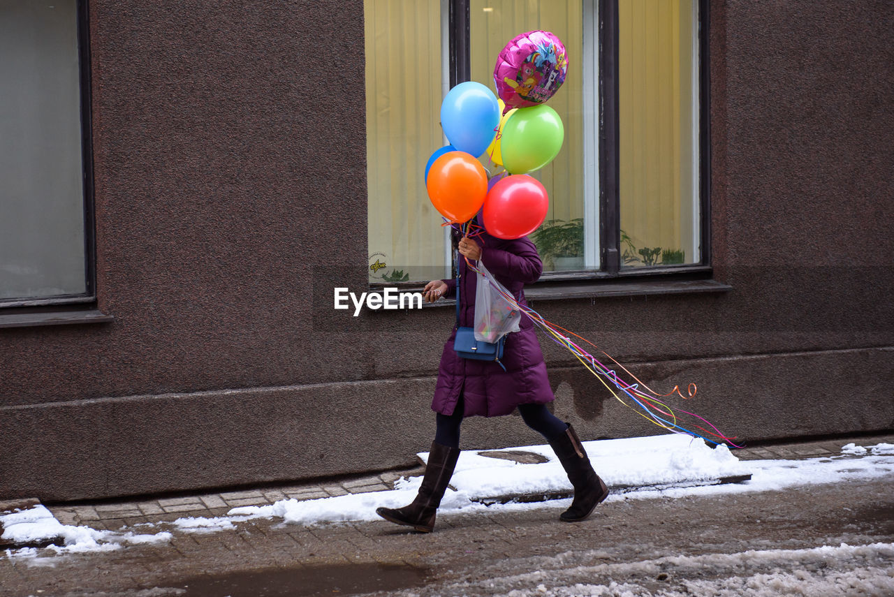 balloon, real people, full length, one person, day, architecture, building exterior, winter, built structure, holding, snow, standing, women, lifestyles, childhood, child, leisure activity, building, outdoors, obscured face