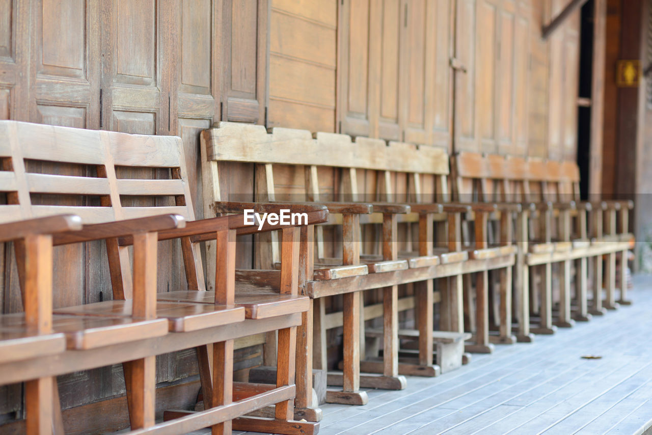 wood - material, seat, chair, absence, no people, table, furniture, empty, in a row, brown, day, arrangement, outdoors, architecture, selective focus, repetition, focus on foreground, bench, wood