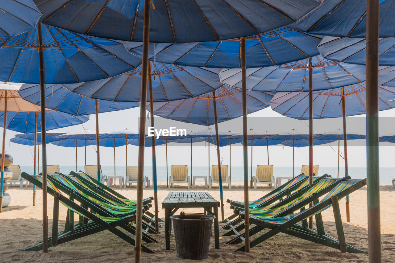 chair, seat, beach, parasol, absence, land, day, umbrella, nature, no people, shade, water, lounge chair, sunshade, protection, sky, deck chair, security, empty, beach umbrella, outdoors, outdoor chair, order