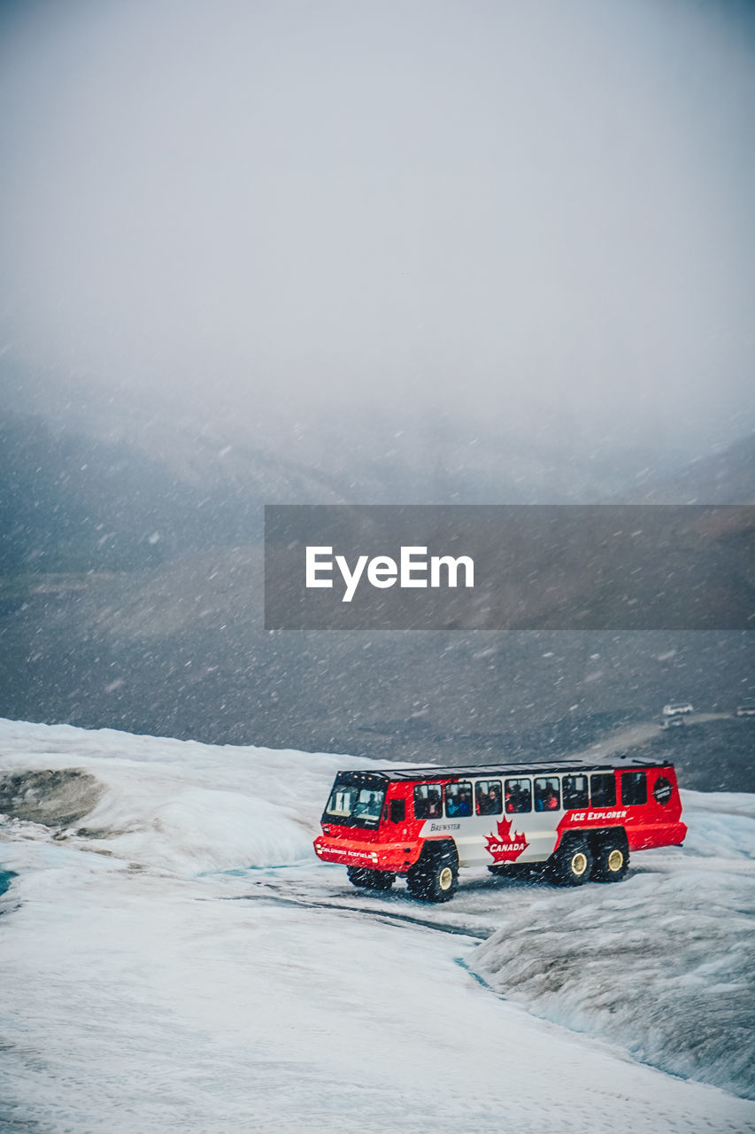winter, cold temperature, transportation, mode of transportation, snow, land vehicle, motor vehicle, car, nature, beauty in nature, mountain, scenics - nature, day, white color, red, no people, sky, environment, land, extreme weather, snowcapped mountain, blizzard, snowing