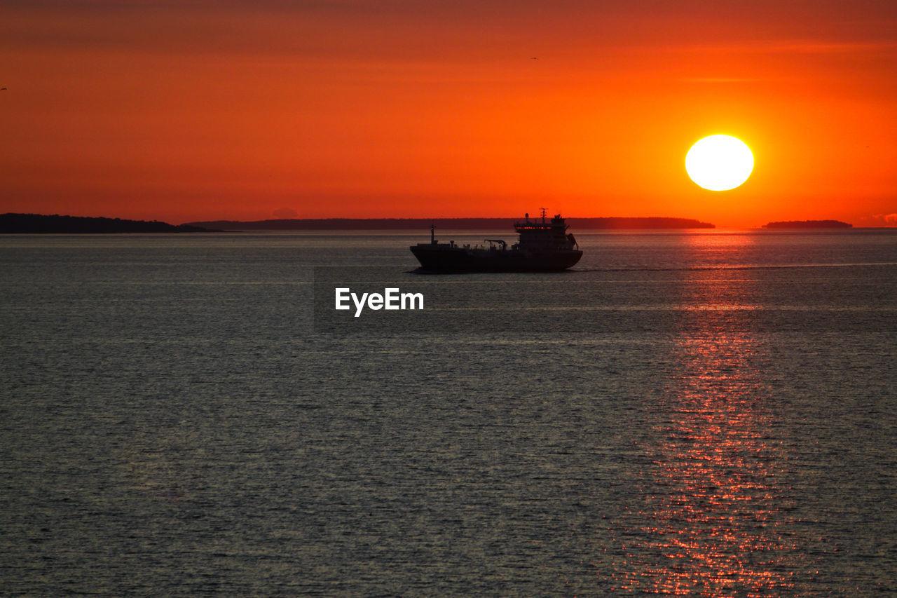 Boat sailing in sea against orange sky in baltic sea