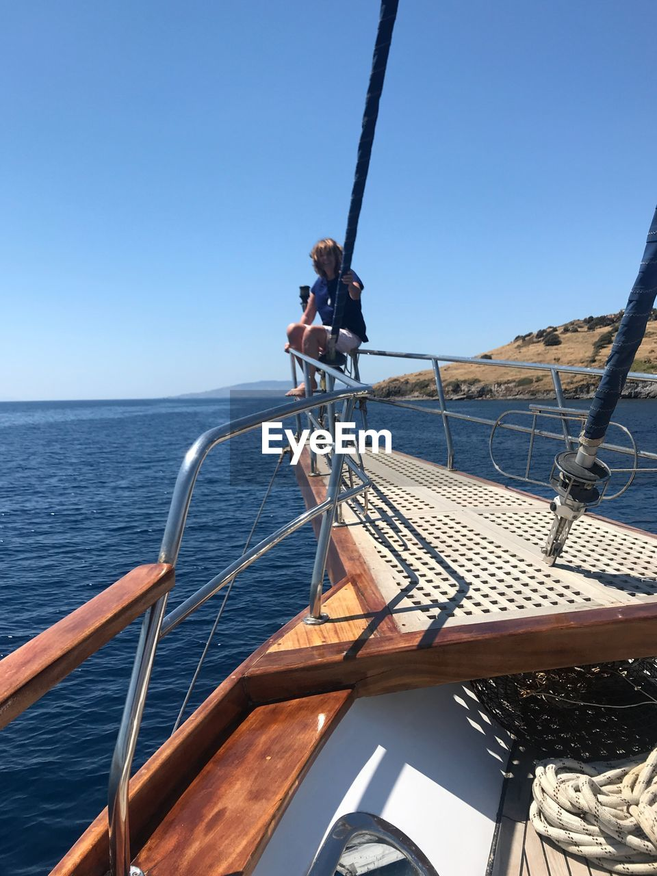 Woman Sitting On Railing Of Sailboat In Sea Against Clear Sky