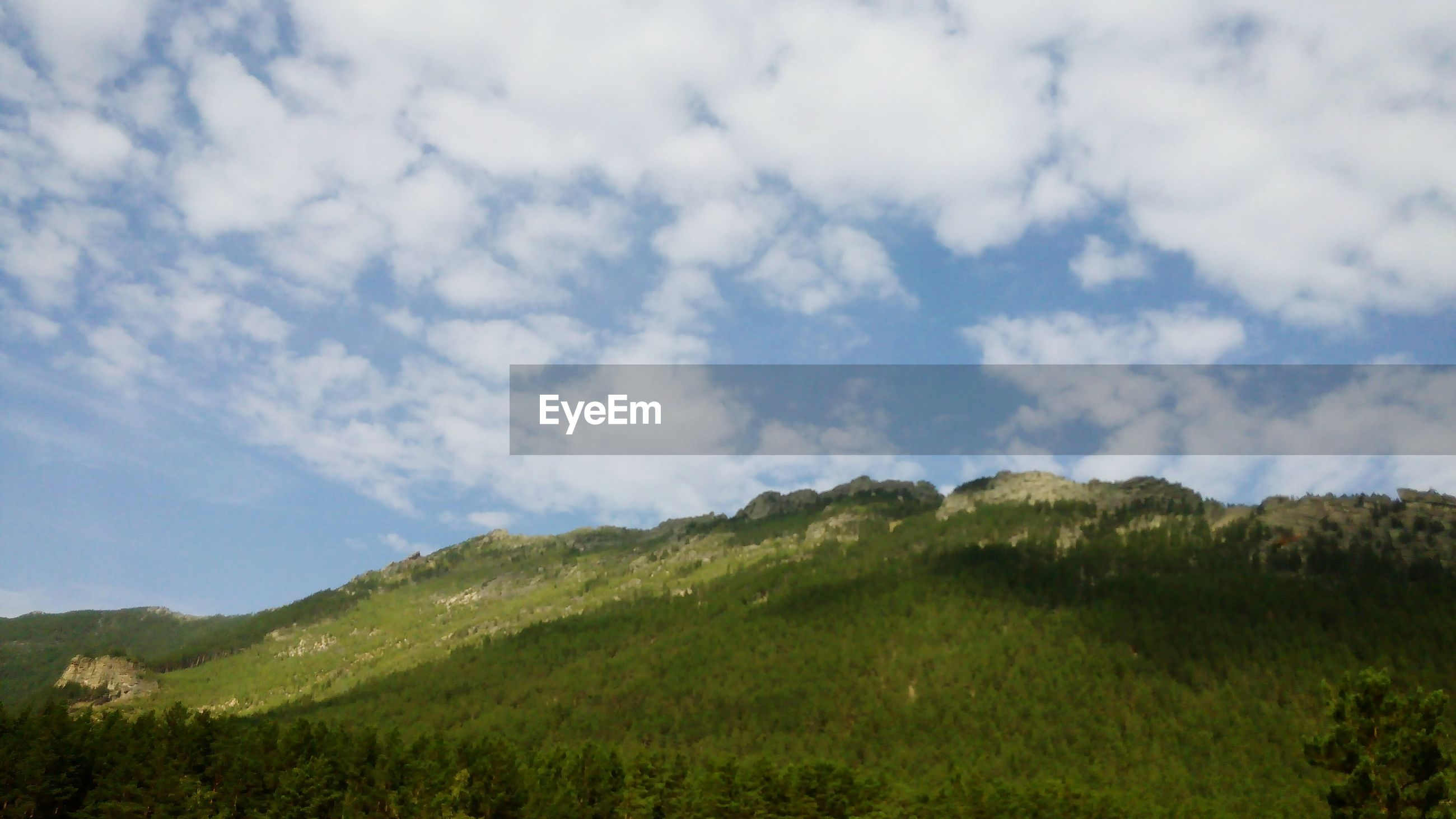 sky, mountain, tranquil scene, tranquility, scenics, landscape, beauty in nature, cloud - sky, grass, nature, green color, cloud, non-urban scene, mountain range, cloudy, tree, growth, hill, idyllic, remote