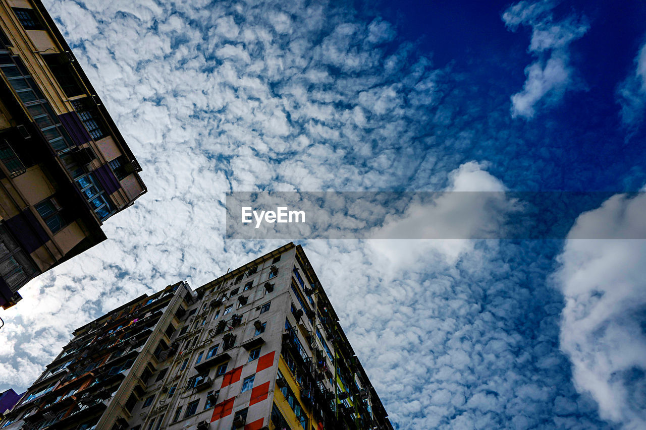 building exterior, sky, built structure, architecture, low angle view, cloud - sky, building, city, nature, no people, day, residential district, outdoors, window, hanging, office building exterior, tall - high, multi colored, high section, directly below, apartment