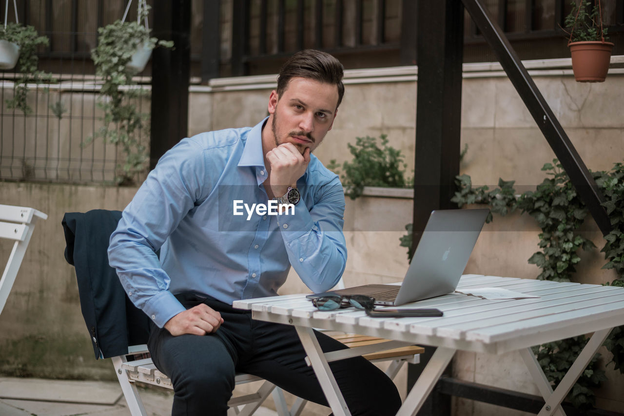 Portrait of businessman using laptop while sitting on table outdoors