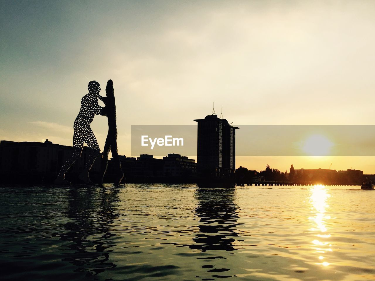 water, waterfront, reflection, sunset, sky, architecture, river, outdoors, real people, built structure, building exterior, standing, silhouette, full length, men, nature, one person, lifestyles, day, beauty in nature, city, people