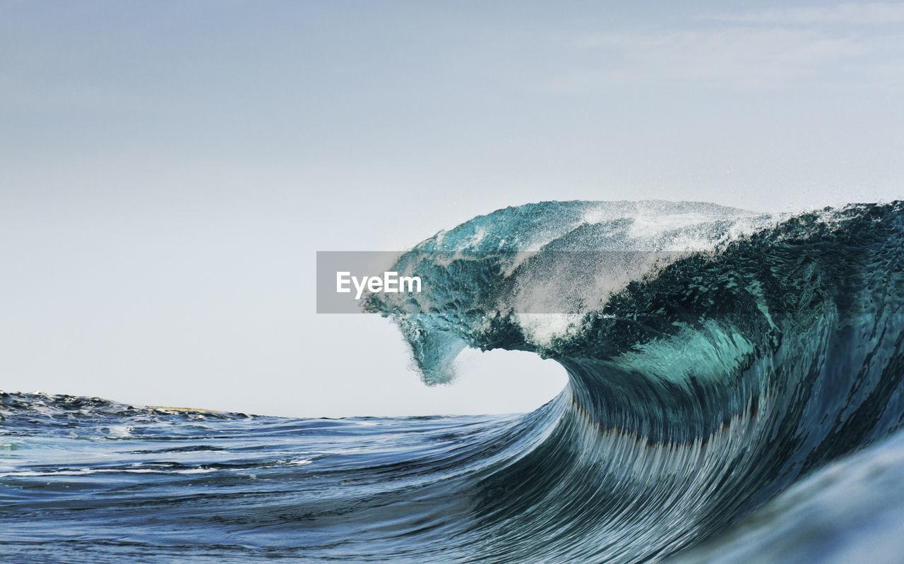 Breaking Sea Wave Against Clear Blue Sky