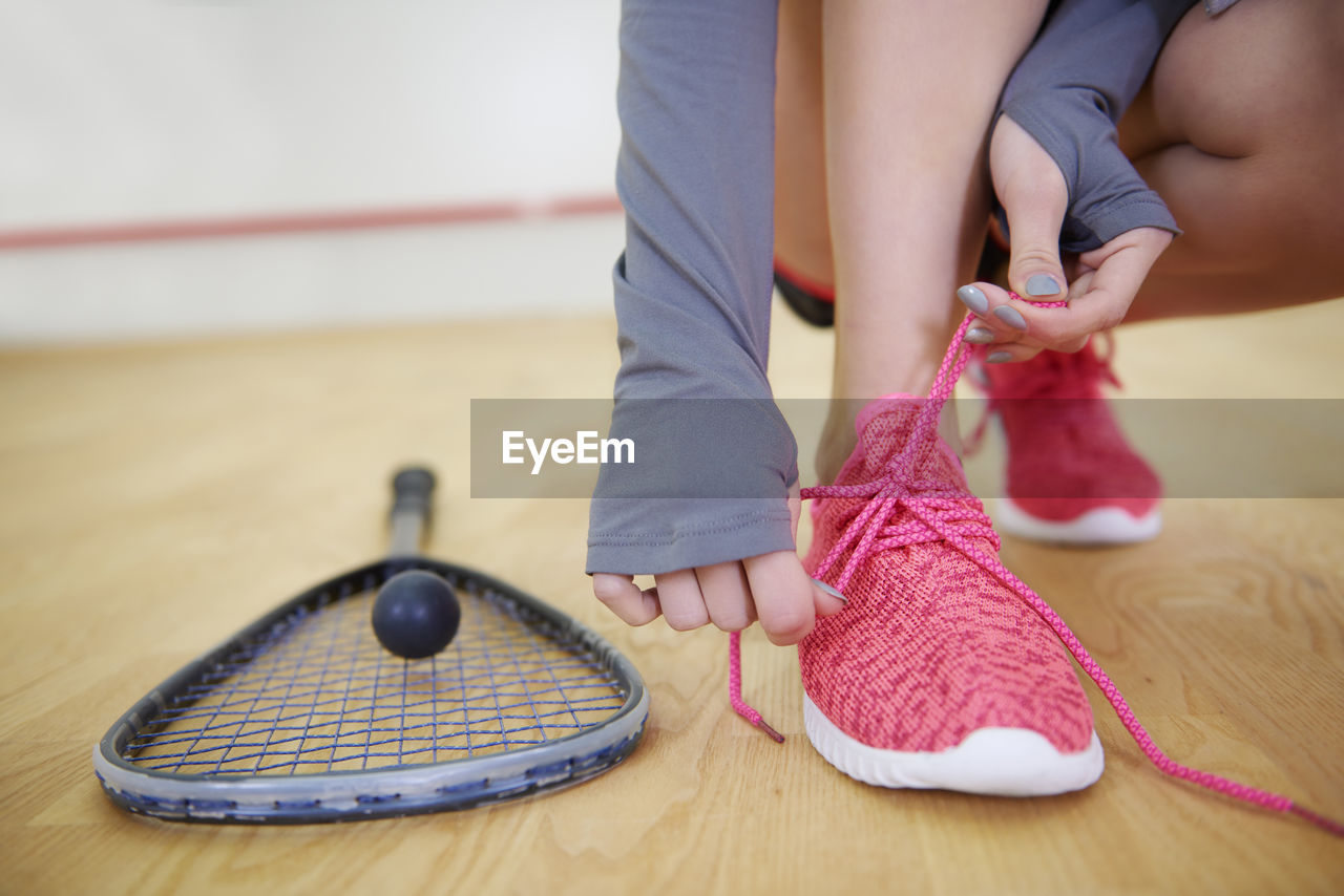 Low section of woman tying shoelace by racket on floor