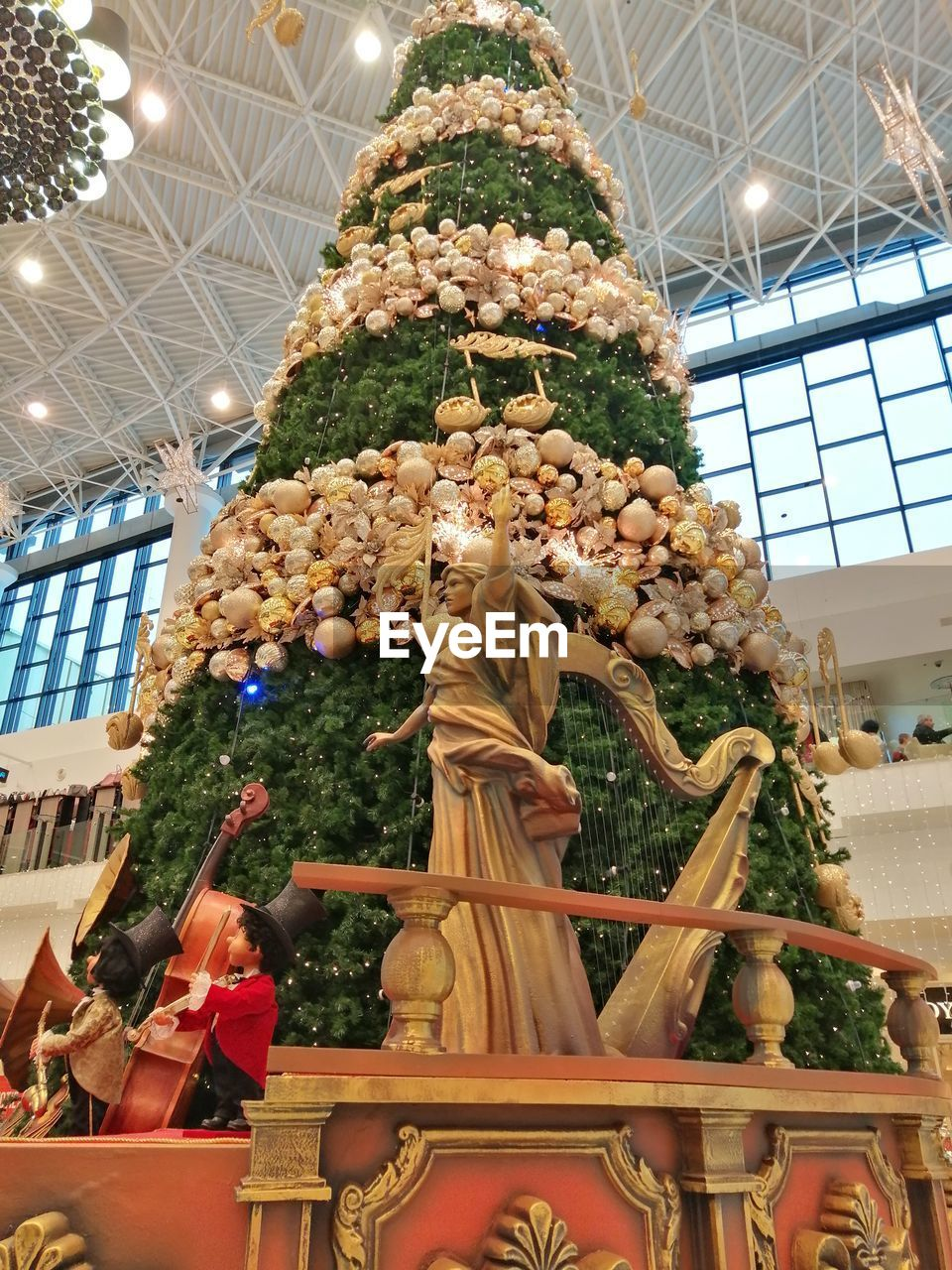 christmas, indoors, decoration, low angle view, christmas decoration, no people, celebration, christmas tree, holiday, christmas ornament, ceiling, illuminated, representation, holiday - event, art and craft, built structure, human representation, architecture, celebration event