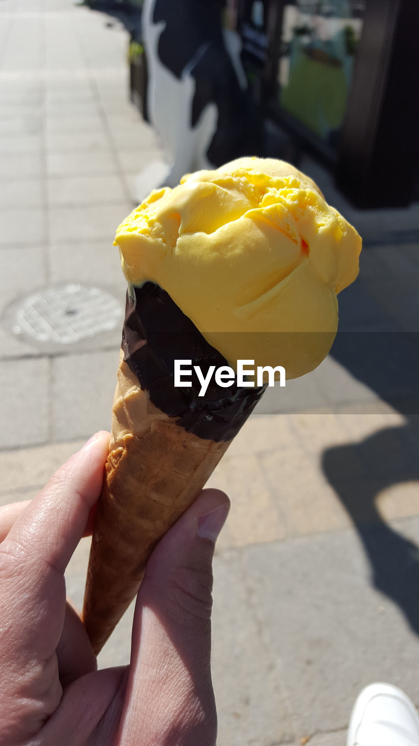 Cropped image of hand holding ice cream on street