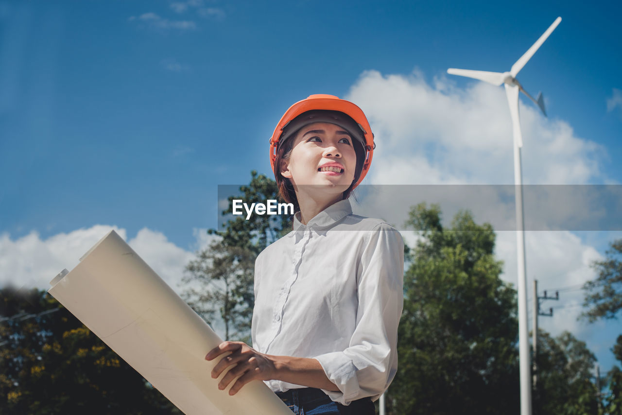 Engineer holding blueprint while working at industry