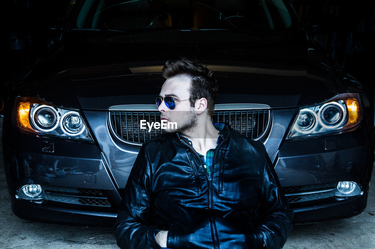 Front View Of Man Sitting Against Car