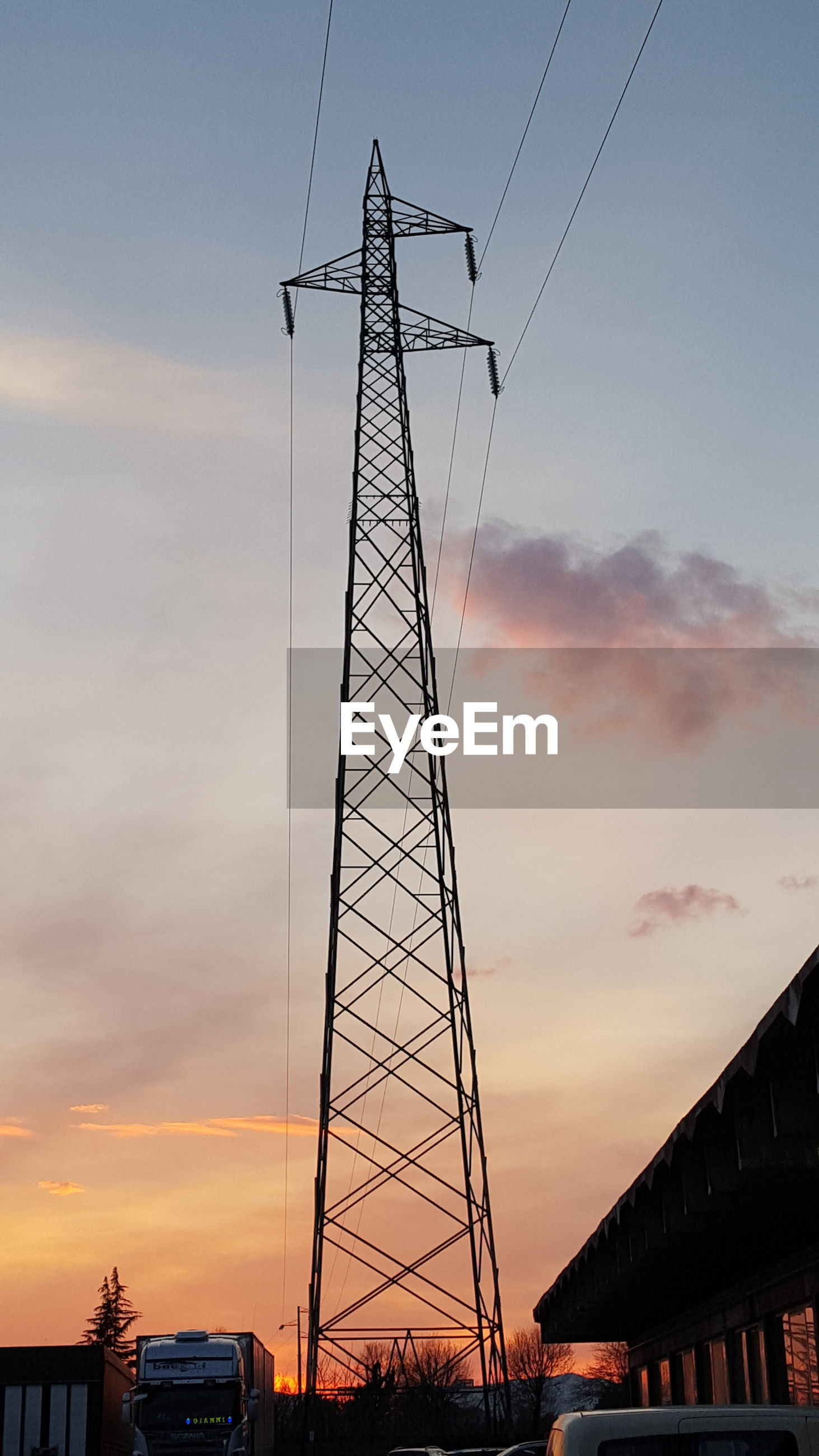 Low angle view of electricity pylon against the sky