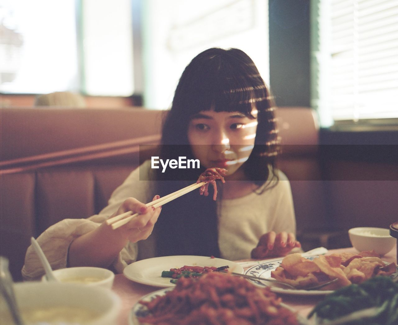 food and drink, table, indoors, real people, food, one person, front view, lifestyles, elementary age, eating, sitting, home interior, childhood, chopsticks, looking at camera, holding, plate, headshot, girls, healthy eating, freshness, portrait, close-up, human hand, ready-to-eat, day, young adult, people
