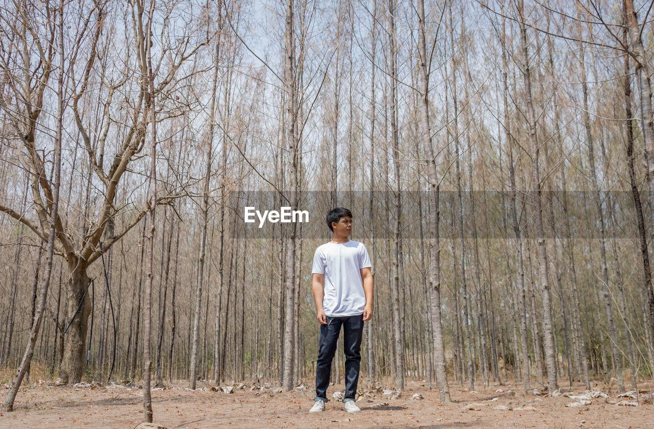 FULL LENGTH OF MAN STANDING ON BARE TREES