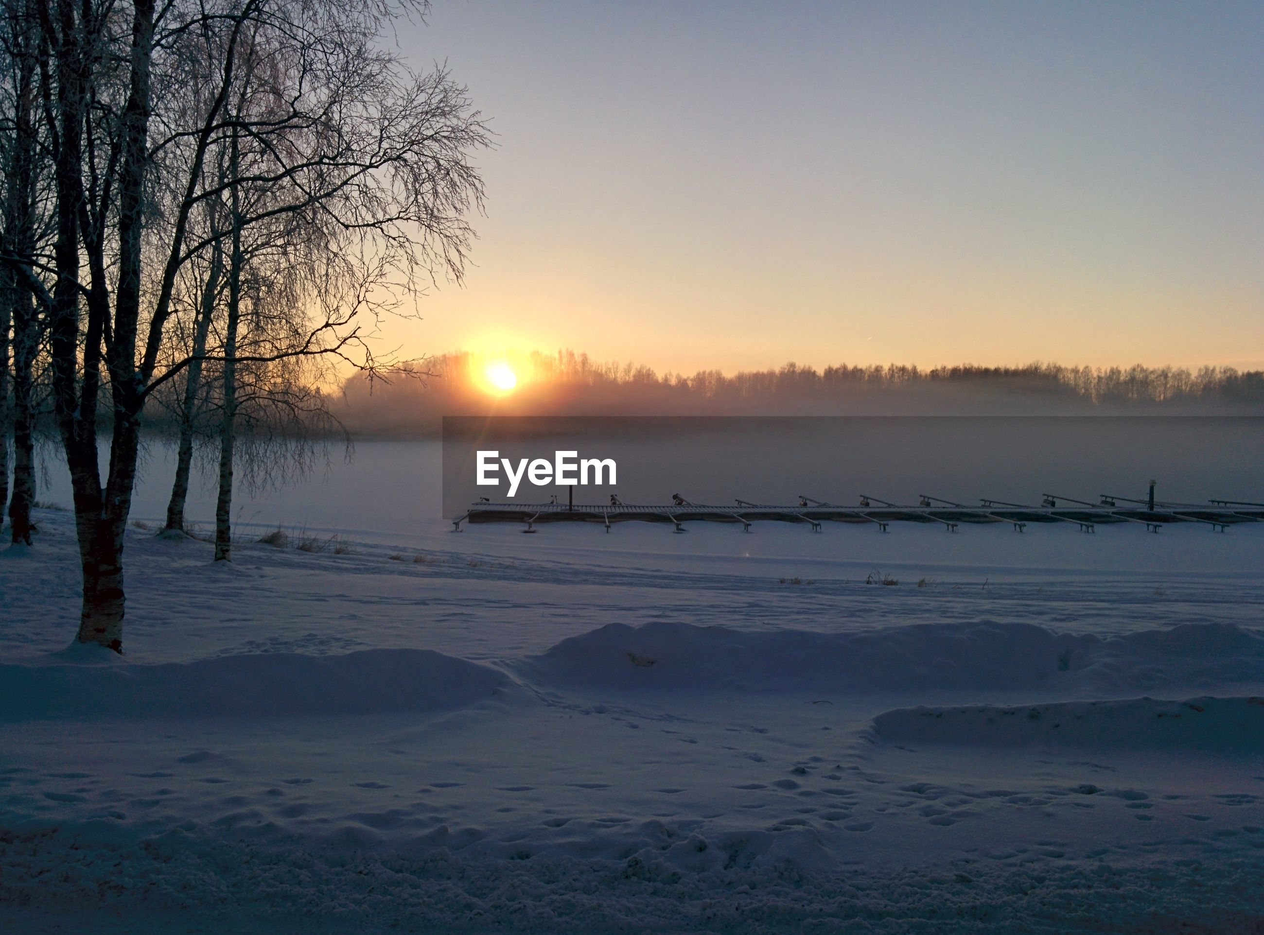 sunset, tranquil scene, tranquility, scenics, sun, beauty in nature, winter, silhouette, bare tree, nature, cold temperature, water, tree, orange color, snow, lake, idyllic, sky, landscape, clear sky