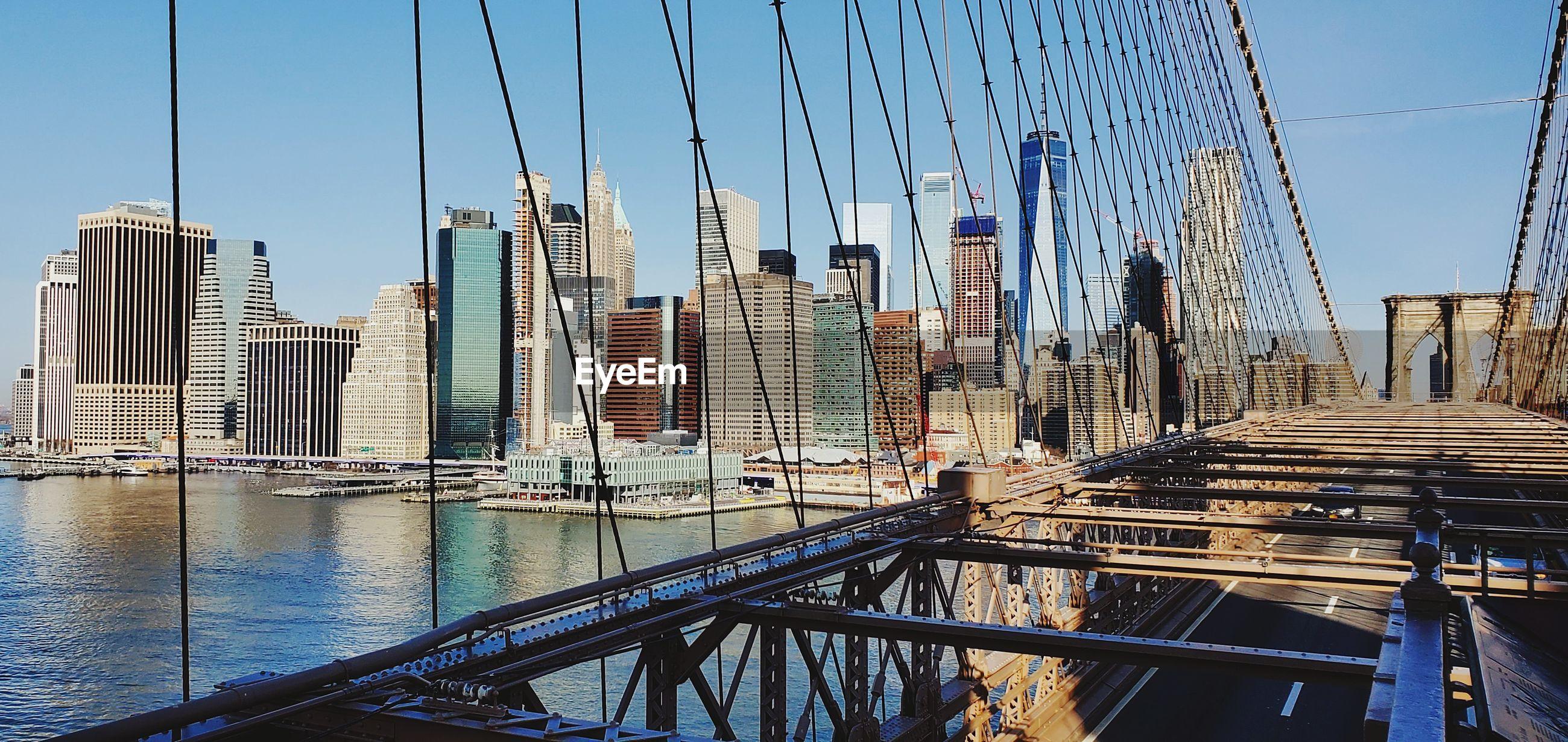 VIEW OF SUSPENSION BRIDGE AGAINST BUILDINGS