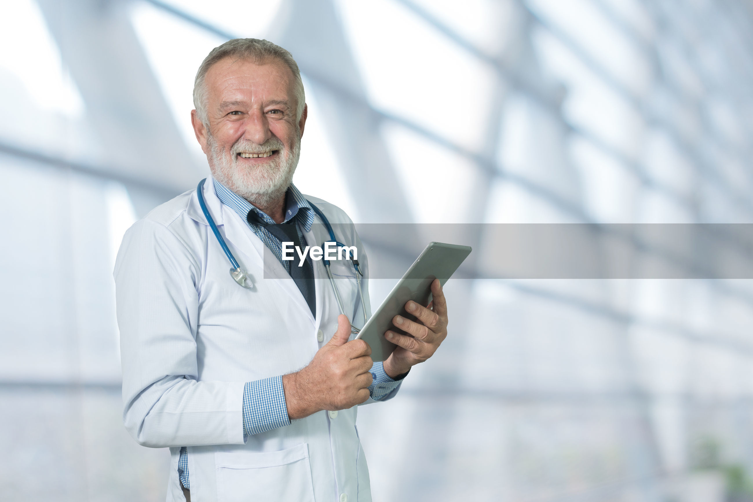 Portrait of smiling senior doctor gesturing thumbs up while holding digital tablet in hospital