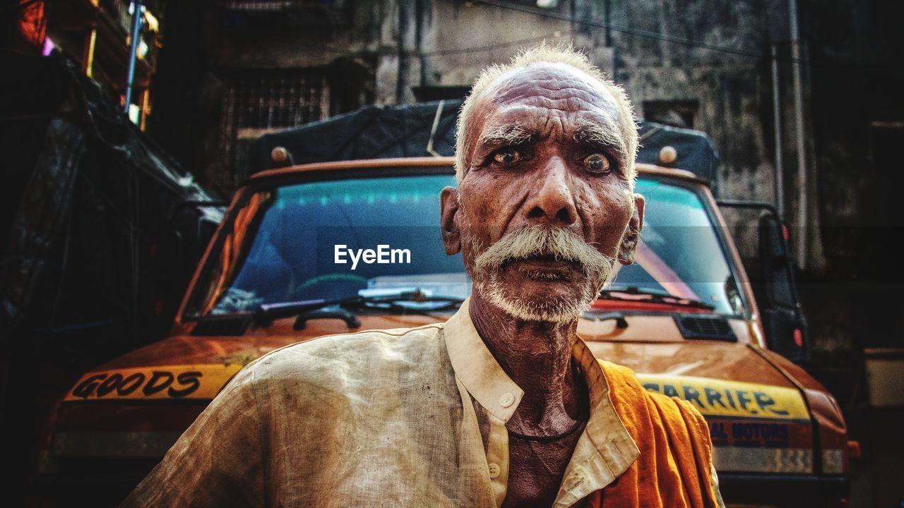 Portrait Of Senior Man Standing Against Truck In City