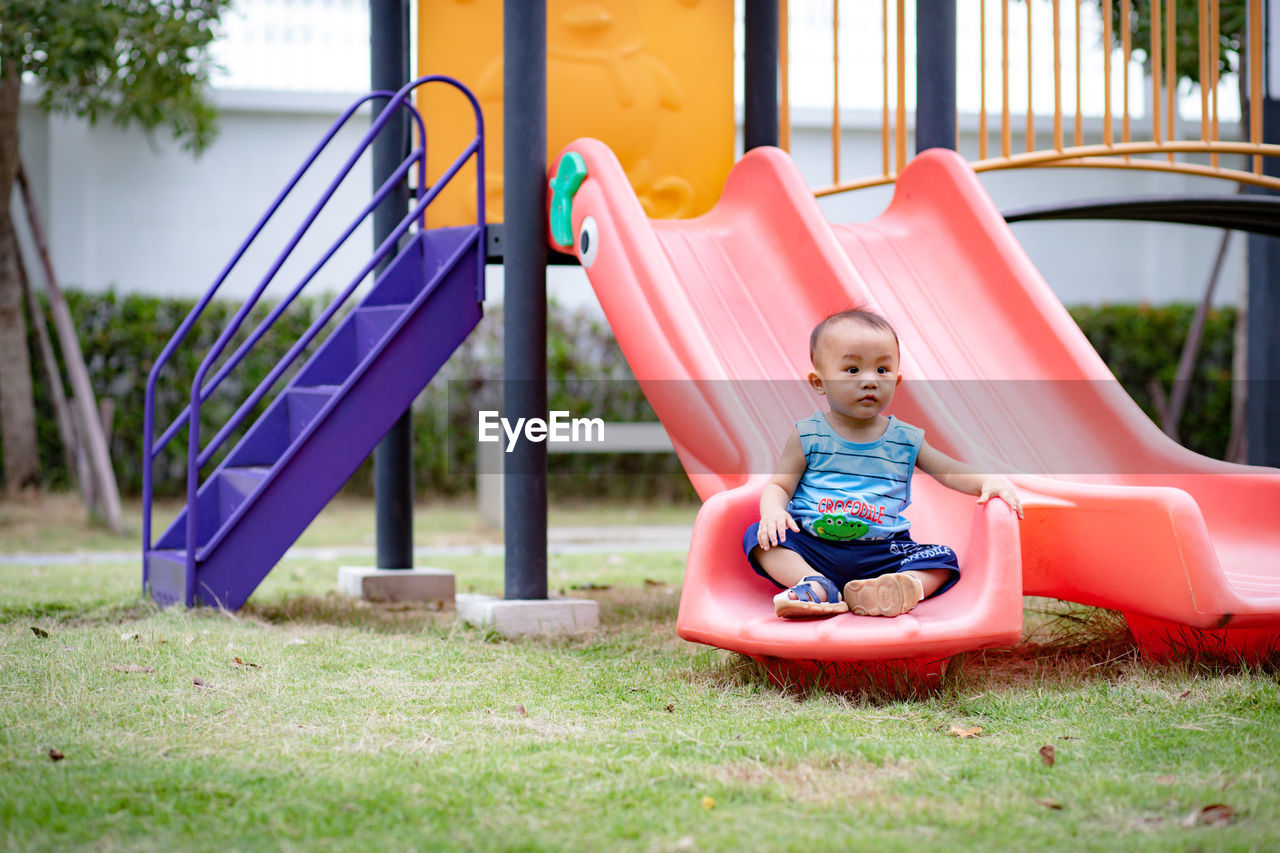 childhood, child, full length, playground, real people, one person, leisure activity, sitting, playing, slide - play equipment, lifestyles, day, innocence, outdoor play equipment, females, fun, enjoyment, outdoors