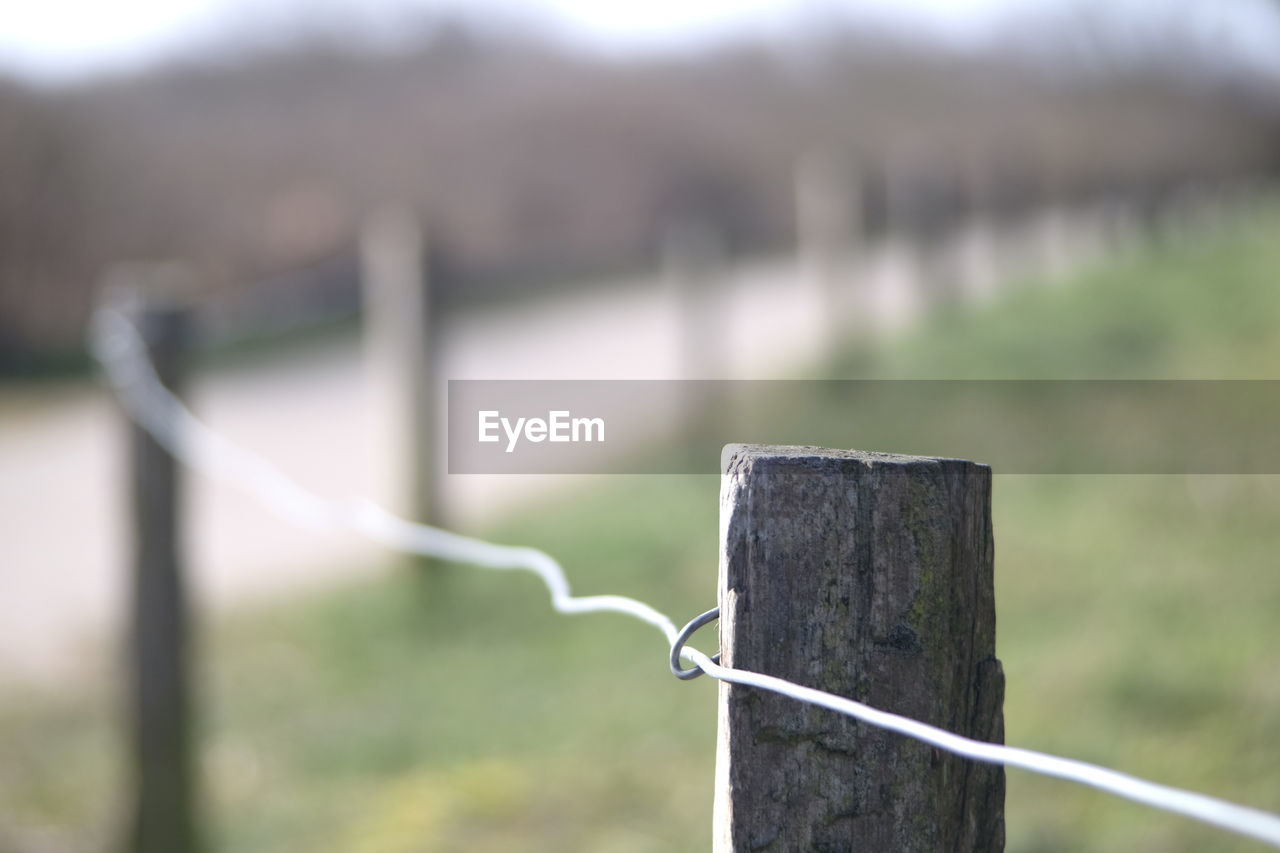 focus on foreground, day, no people, metal, nature, post, close-up, outdoors, wood - material, wooden post, safety, barrier, water, fence, railing, sunlight, boundary, security, protection