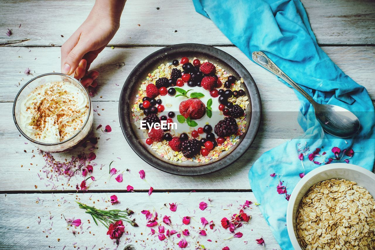 food and drink, food, freshness, fruit, table, healthy eating, human hand, one person, high angle view, hand, wellbeing, indoors, ready-to-eat, berry fruit, eating utensil, kitchen utensil, bowl, sweet, human body part, sweet food, breakfast, meal, temptation, glass