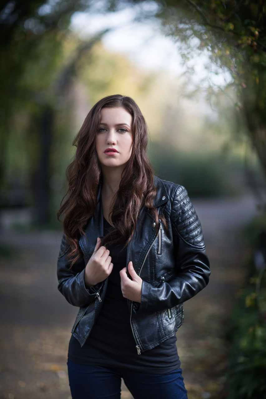 Portrait Of Beautiful Woman Wearing Leather Jacket Standing On Footpath At Park