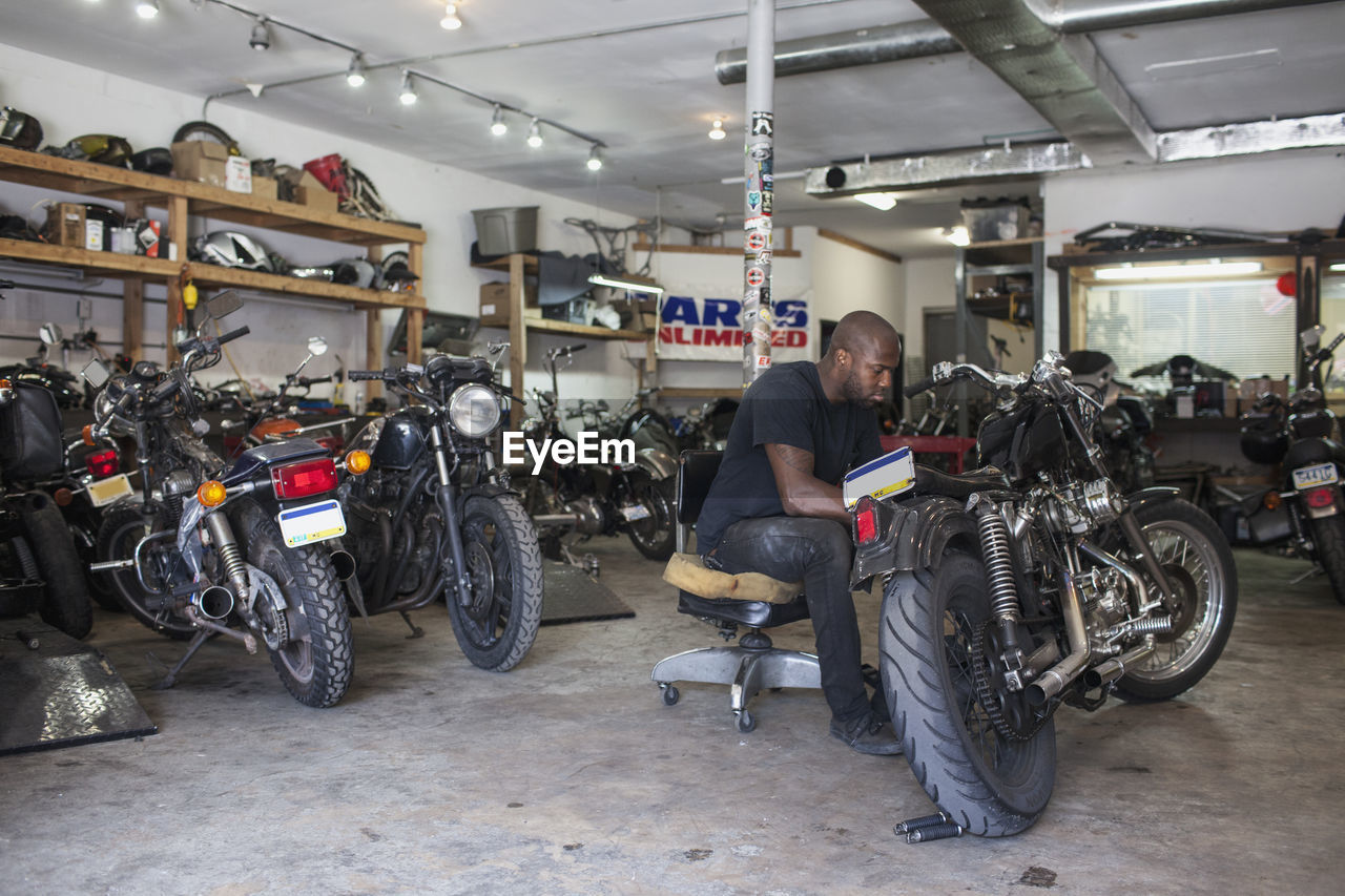 transportation, mode of transportation, motorcycle, land vehicle, people, men, shopping, indoors, store, small business, real people, occupation, adult, retail, business, full length, bicycle, casual clothing, mechanic, auto repair shop, bicycle shop, garage