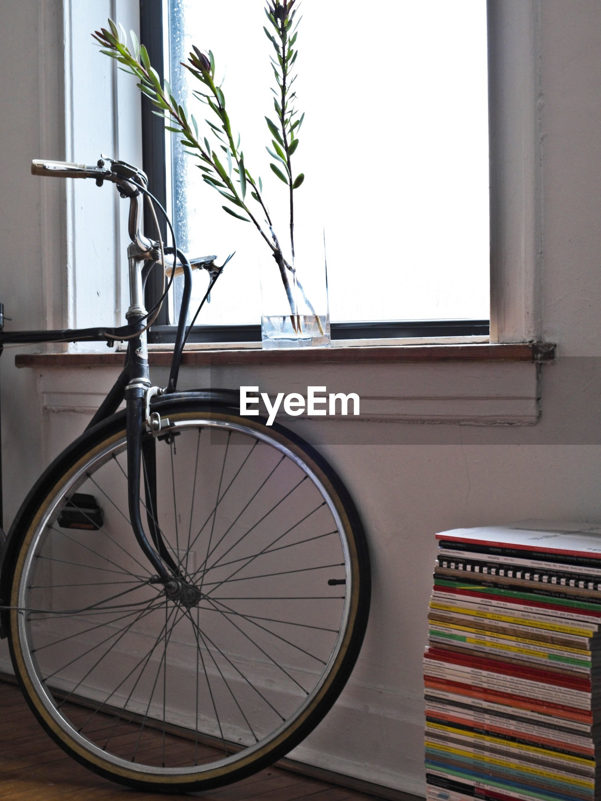 Bicycle parked safely inside house next to stack of book against window wall