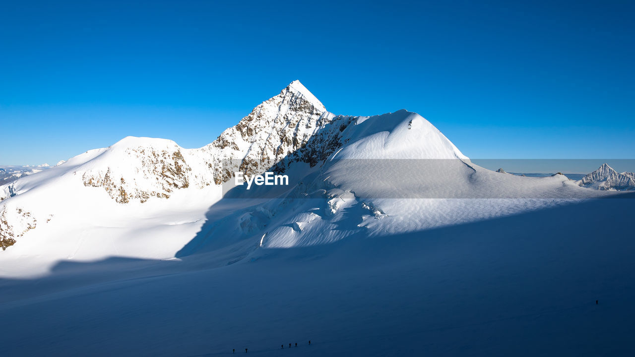 mountain, tranquil scene, beauty in nature, tranquility, scenics, nature, snow, blue, snowcapped mountain, winter, non-urban scene, cold temperature, day, outdoors, low angle view, clear sky, no people, physical geography, mountain range, sky