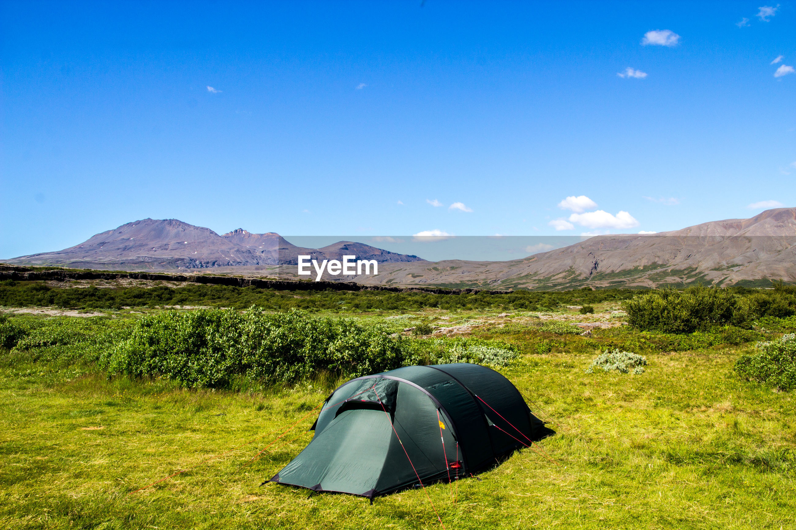 High angle view of tent on grassy mountain against sky