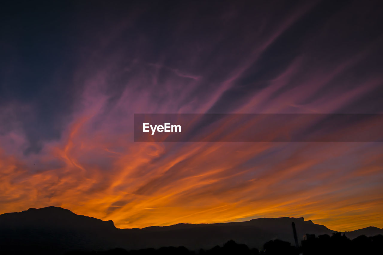 sunset, beauty in nature, sky, scenics - nature, cloud - sky, tranquil scene, silhouette, orange color, mountain, tranquility, idyllic, no people, non-urban scene, nature, dramatic sky, outdoors, environment, mountain range, low angle view, landscape, mountain peak, romantic sky
