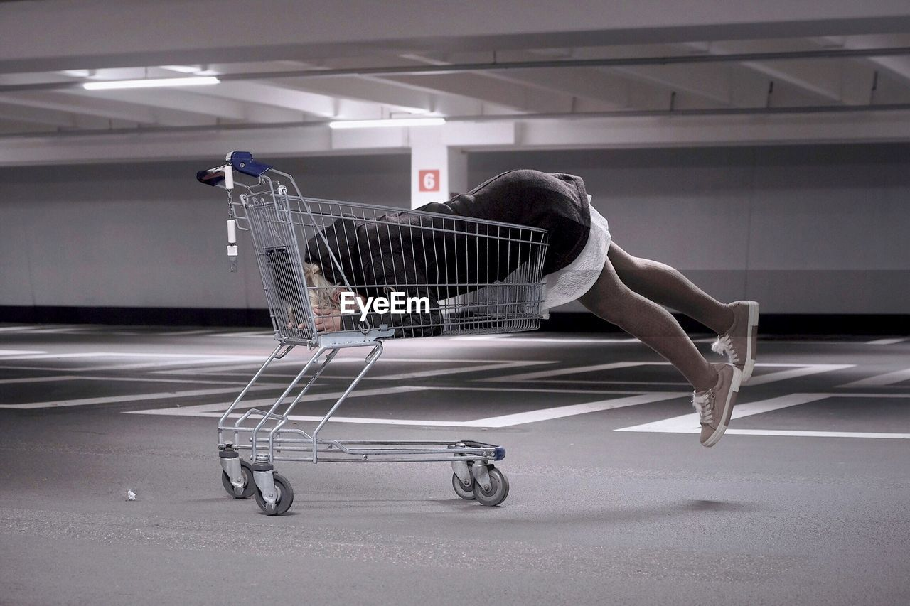 Side View Of Woman Lying In Shopping Cart At Parking Garage
