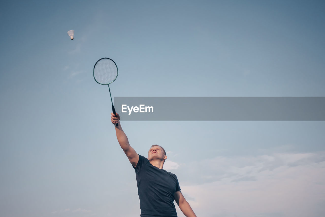 Low angle view of person playing badminton against sky