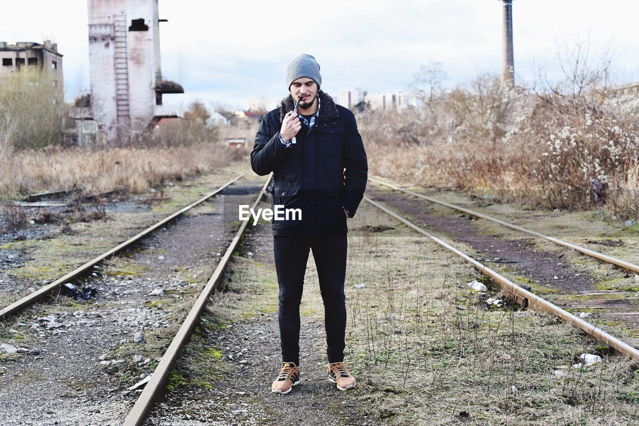 Full Length Of Man Smoking Pipe At Railroad Track