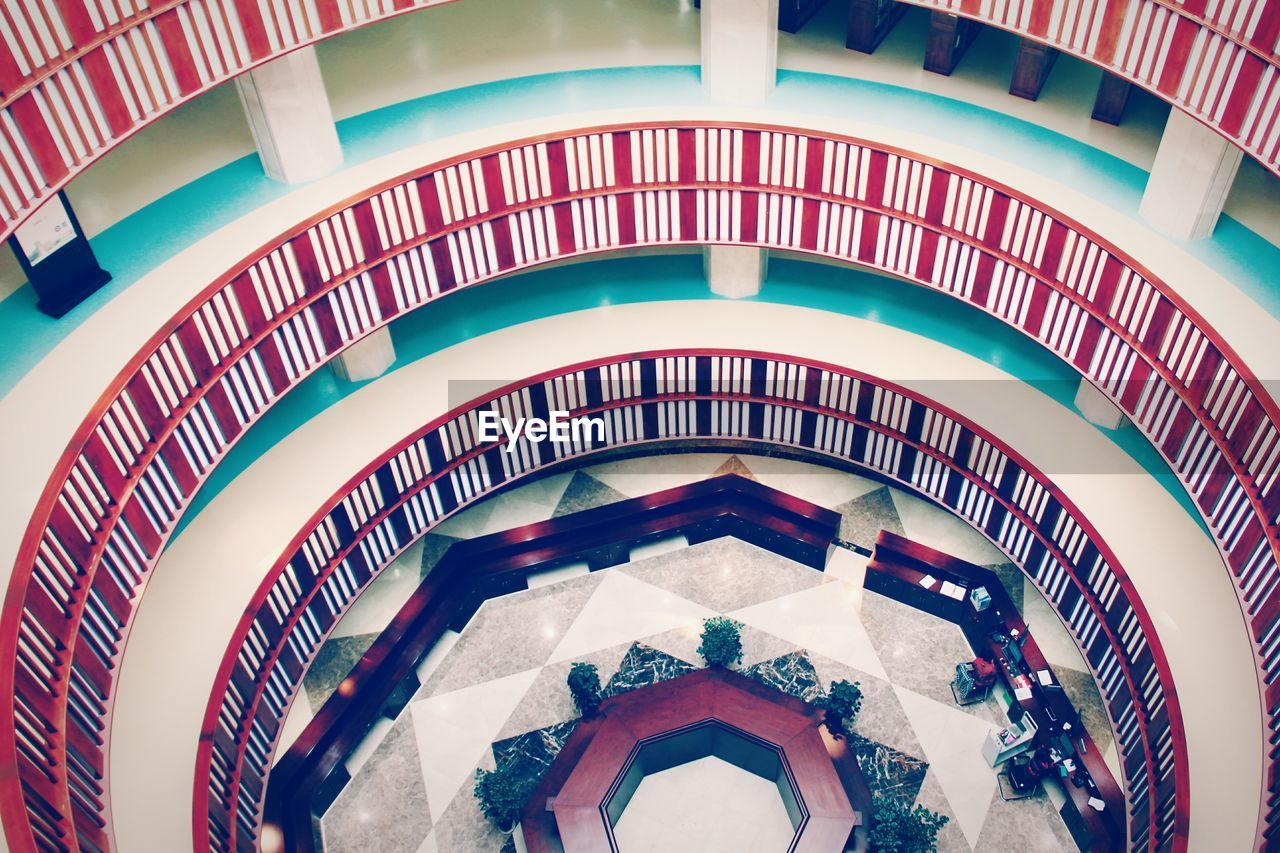 architecture, built structure, indoors, real people, men, lifestyles, high angle view, group of people, people, modern, building, adult, arch, leisure activity, women, pattern, railing, spiral, incidental people, luxury
