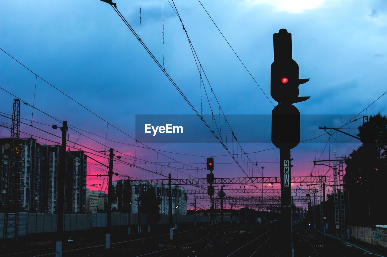 sky, cable, electricity, transportation, sunset, power line, sign, railroad track, connection, track, cloud - sky, rail transportation, technology, architecture, nature, railway signal, stoplight, dusk, silhouette, mode of transportation, guidance, outdoors, no people, power supply, light, complexity