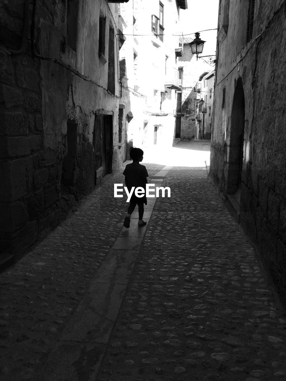 Rear view of boy walking in alley