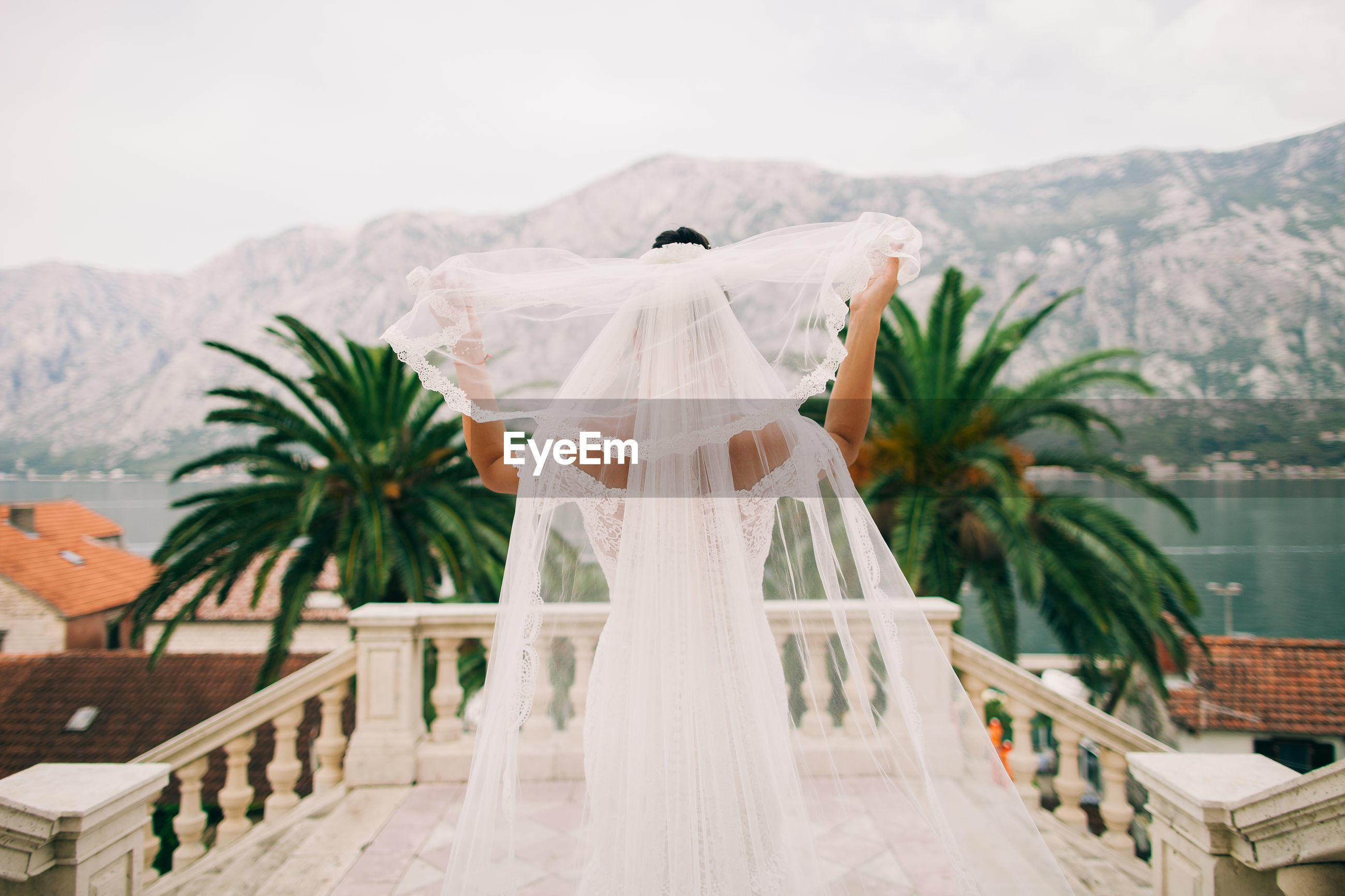 Rear view of bride holding veil at balcony
